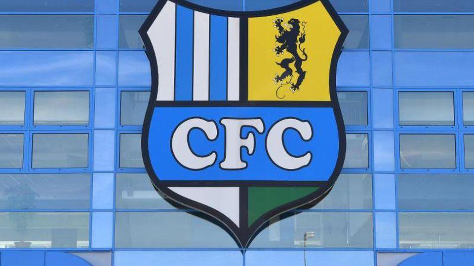 Das Logo des Chemnitzer FC hängt über dem Eingang zum Stadion. Foto: Hendrik Schmidt/zb/dpa/Archivbild