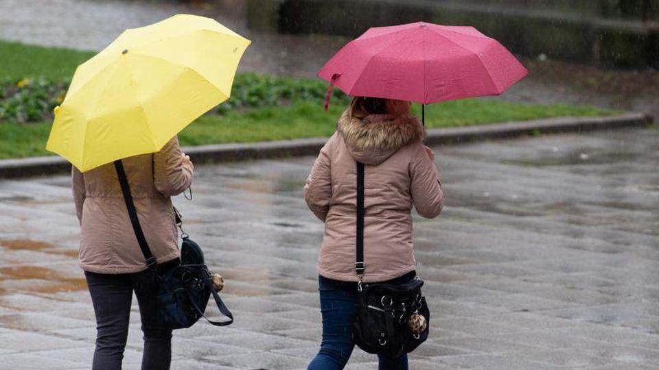 Zwei Frauen sind mit Regenschirmen unterwegs. Foto: Tom Weller/dpa/Archivbild
