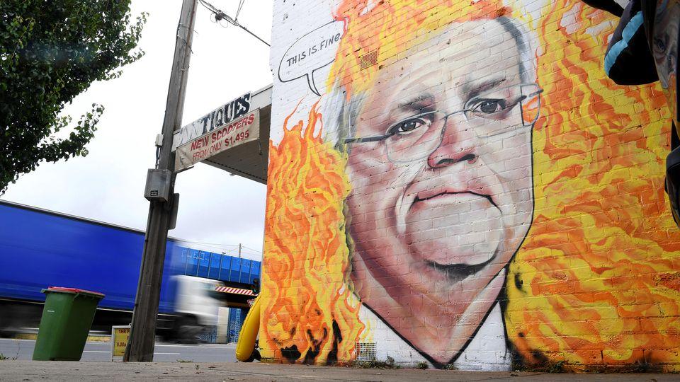 07.01.2020, Australien, Melbourne: Ein Wandgemälde, das den australischen Premierminister Morrison inmitten von Buschfeuerflammen zeigt ist in Tottenham zu sehen. Morrisons Umgang mit der australischen Buschfeuer-Krise wurde zusammen mit der Untätigk