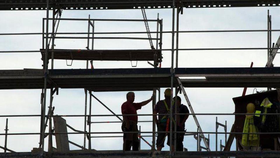 Bauarbeiter zeichnen sich auf einem Gerüst als Silhouette ab. Foto: Sebastian Kahnert/Archivbild