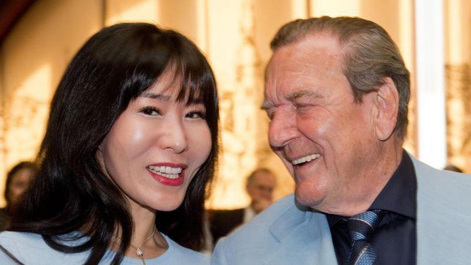 Altbundeskanzler Gerhard Schröder (SPD) steht mit seiner Frau Soyeon bei einem Empfang. Foto: Julian Stratenschulte/dpa/Archivbild