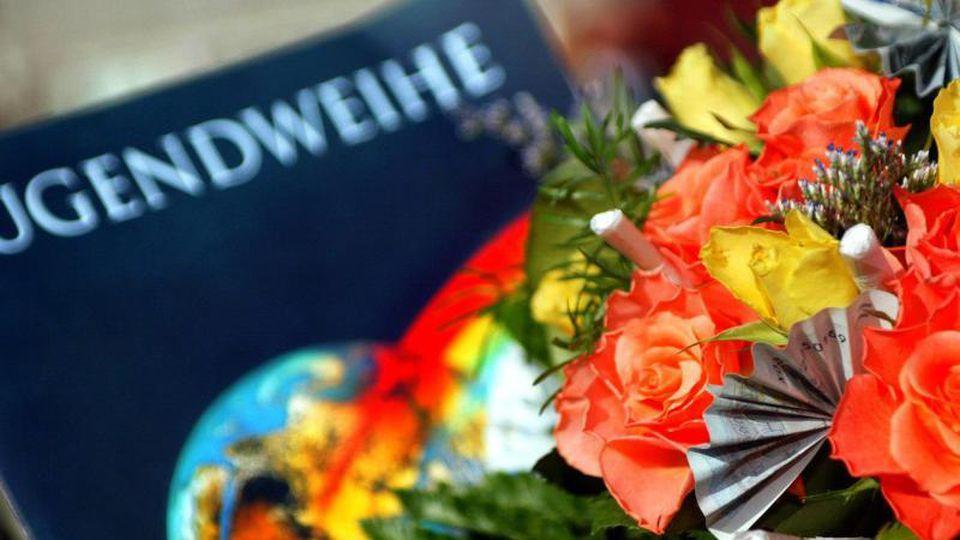Eine Jugendweihe-Urkunde liegt neben einen Blumenstrauß. Foto: Andreas Lander/dpa-Zentralbild/dpa/Symbolbild