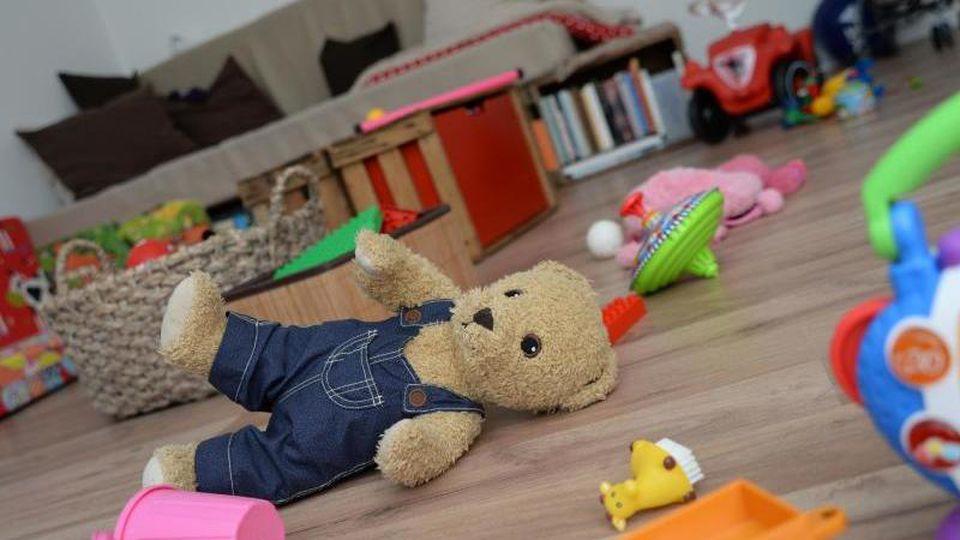 Ein Teddybär und anderes Spielzeug liegt verstreut auf dem Fußboden eines Kinderzimmers. Foto: Andrea Warnecke/dpa-tmn/dpa/Symbolbild