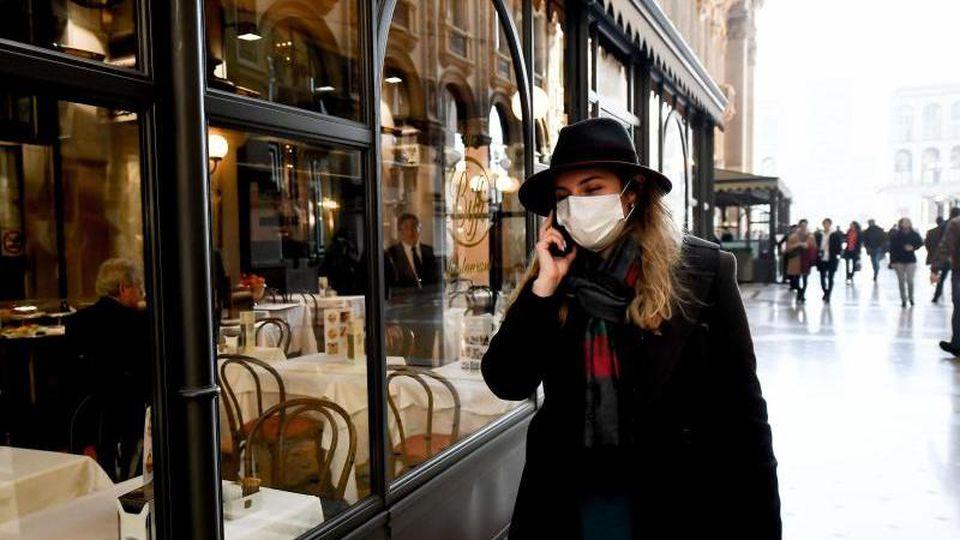 Eine Frau mit Mundschutz vor einem Restaurant in Mailand. Foto: Claudio Furlan/LaPresse via ZUMA Press/dpa