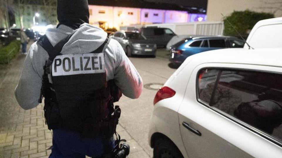 Ein Polizeibeamter steht nach der tödlichen Schießerei in der Nähe eines der Tatorte auf der Straße. Foto: Boris Roessler/dpa
