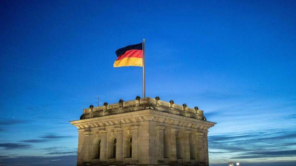 Die Deutschlandfahne weht vor dem Abendhimmel auf dem Reichstagsgebäude im Wind. Foto: Kay Nietfeld/dpa