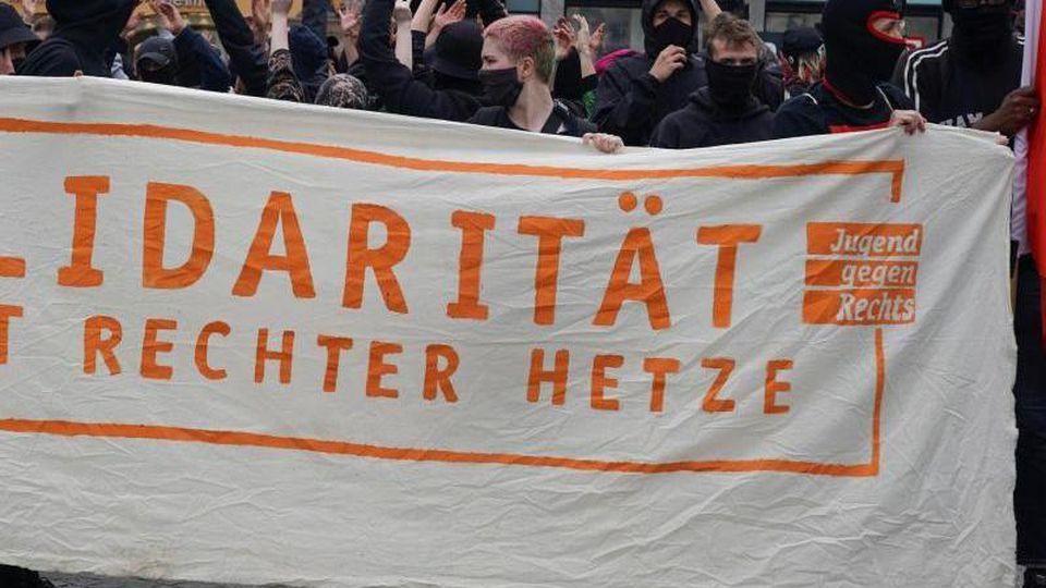 """Teilnehmer der geplante Kundgebung und Demonstration """"Solidarität statt rechter Hetze"""" halten ein Transparent. Foto: Peter Endig/dpa-Zentralbild/dpa"""