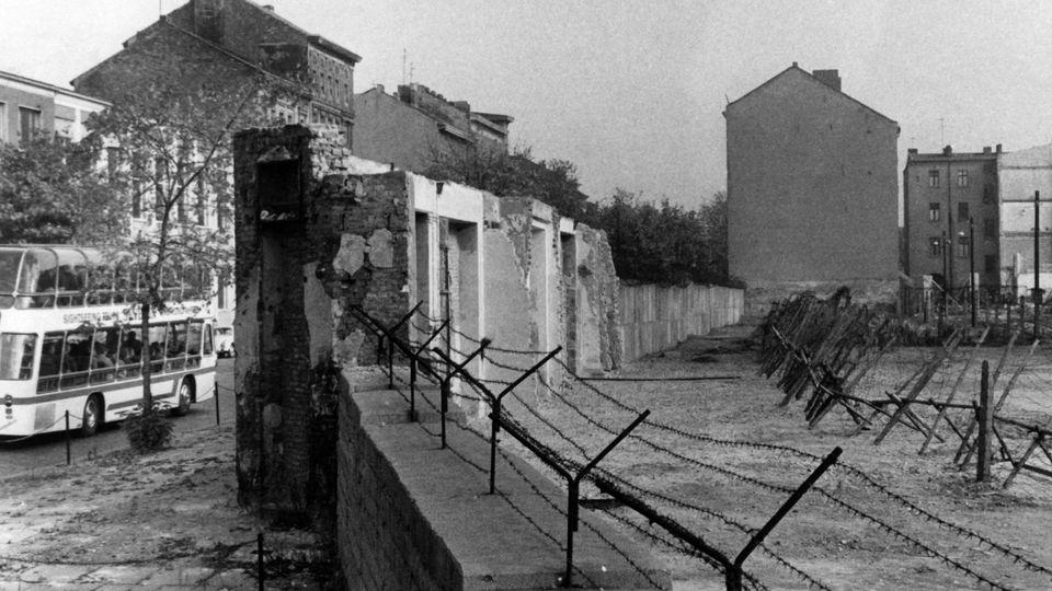 ARCHIV - Blick auf die Berliner Mauer mit Sperranlagen und Todesstreifen am 22.10.1965 in der Bernauer Straße in Berlin-Wedding. Gut zu erkennen sind auch noch die Reste der Häuser die nach und nach für den Mauerbau abgerissen wurden. Jahrestage des