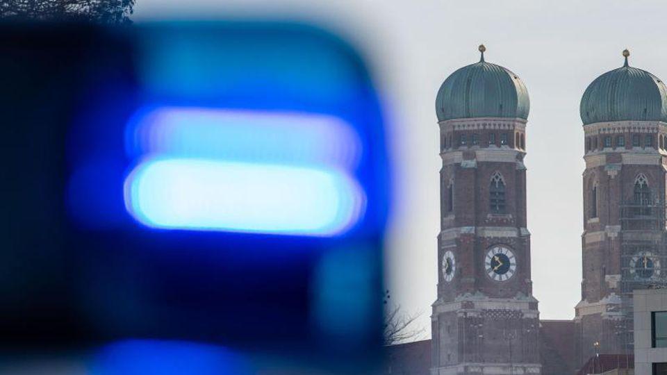Ein Blaulicht einer Polizeistreife ist vor den Türmen der Frauenkirche zu sehen. Foto: Lino Mirgeler/dpa/Archivbild