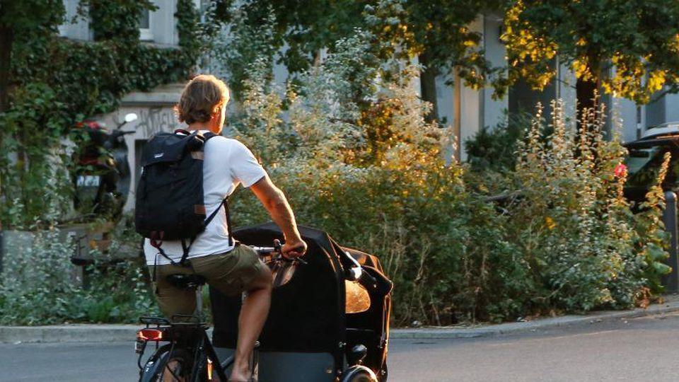 Ein Mann fährt mit einem Lastenfahrrad auf einer Straße. Foto: Gerald Matzka/Archivbild
