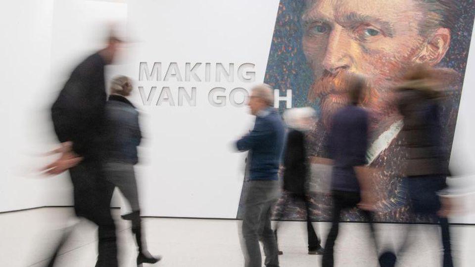 Besucher gehen an einem vergrößerten Selbstporträt des Künstlers vorbei. Foto: Boris Roessler/dpa