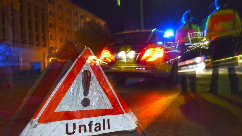 """Ein Warndreieck mit dem Schriftzug """"Unfall"""" steht vor einem Polizeifahrzeug. Foto: Patrick Seeger/dpa/Illustration"""