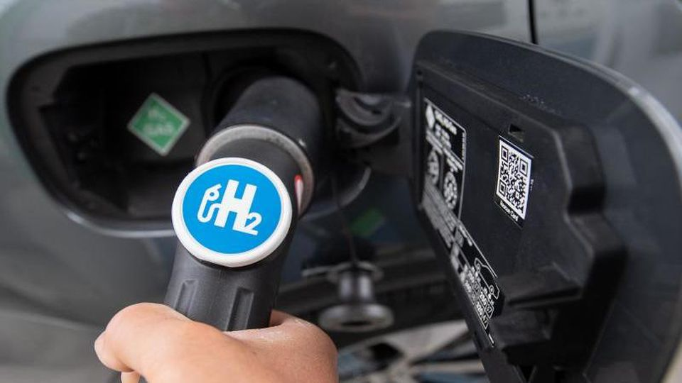 Ein Mann hält den Zapfhahn einer Wasserstoffzapfsäule an den Stutzen eines Wasserstoffautos. Foto: Sebastian Gollnow/dpa/Symbolbild