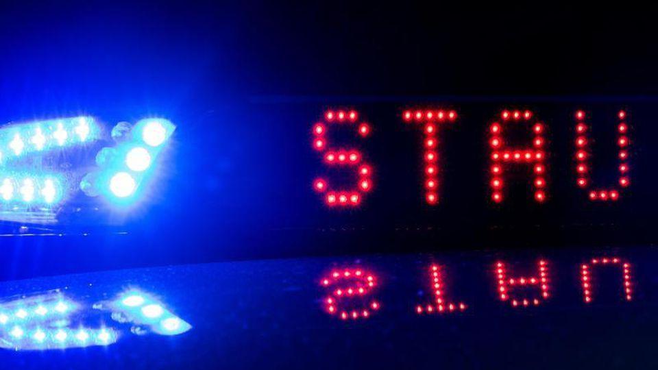 """Das Blaulicht auf einem Polizeifahrzeug der leuchtet, während sich das Display mit dem Wort """"Stau"""" spiegelt. Foto: Monika Skolimowska/zb/dpa/Symbolbild"""