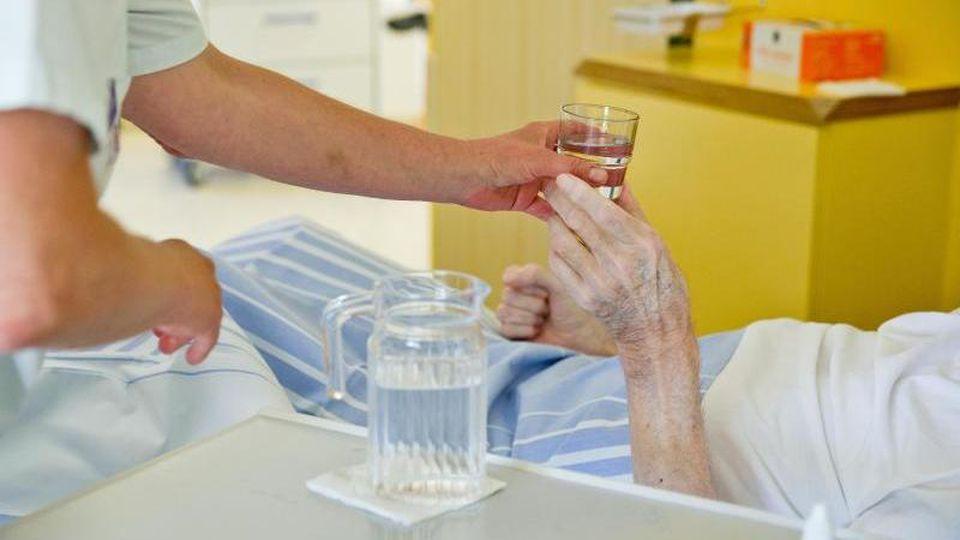 Eine Krankenpflegerin reicht einem Patienten in einem Klinikum ein Glas Wasser. Foto: Daniel Karmann/dpa/Archivbild