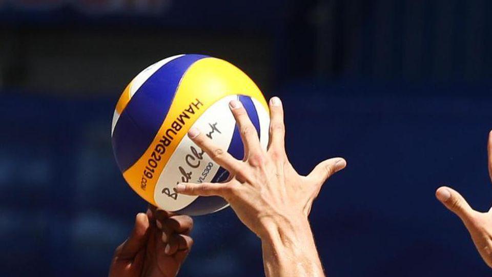 Hände greifen nach einem Volleyball. Foto: Christian Charisius/dpa/Archivbild