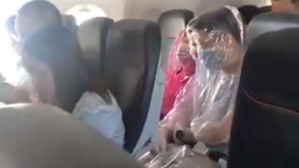 Aus Angst vor dem Coronavirus? Flugzeug-Passagiere wickeln sich in Plastik ein.