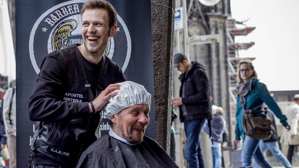 """Der """"Barber Angel"""" wäscht die Haare des obdachlosen Menschen unter der Waschhaube."""