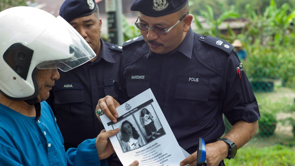 August 9, 2019, Kuala Lumpur, MALAYSIA: A Royal Malaysian Police officer hands a poster to a motodriver bearing a portrait of the missing girl Nora Quoirin,15, in Seremban, Negeri Sembilan, Malaysia on August 9, 2019.