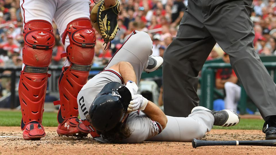 Home Plate Umpire Tim Timmons yells for help after Atlanta Braves Charlie Culberson lies on the grou