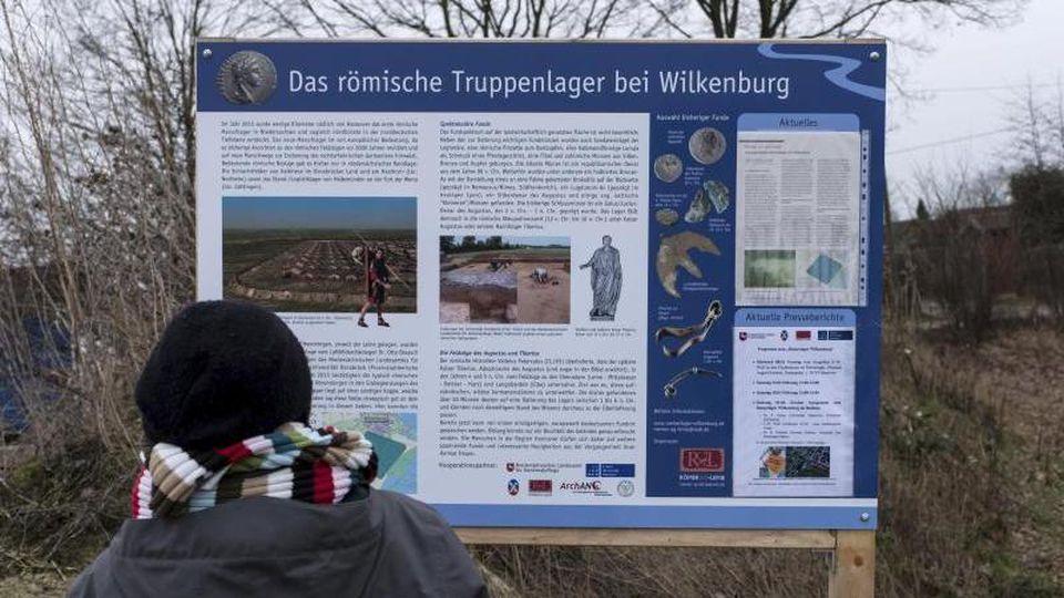 Menschen stehen in Hemmingen vor einer Informationstafel neben der Ausgrabungsstelle eines Römerlagers. Foto: Peter Steffen/Archivbild