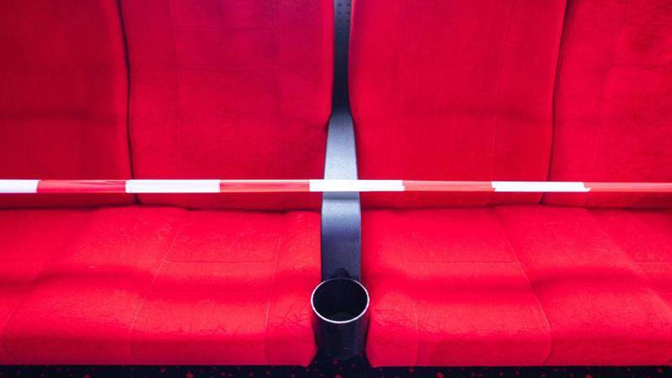Rote Kinositze sind mit einem Sperrband abgesperrt. Foto: Robert Michael/dpa-Zentralbild/dpa/Symbolbild