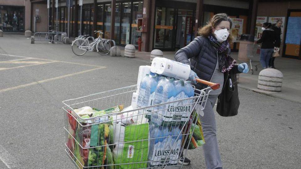 Eine Frau trägt eine Atemschutzmaske und zieht einen Einkaufswagen. Foto: Luca Bruno/AP/dpa
