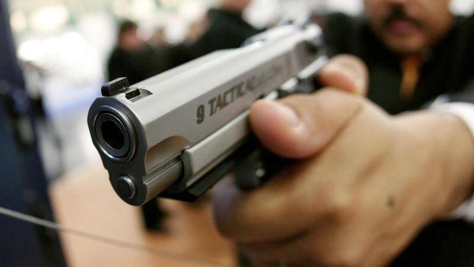 Ein Mitarbeiter des US-amerikanischen Herstellers Smith & Wesson auf der Waffenmesse in Nürnberg. Foto: Daniel Karmann / picture alliance / dpa