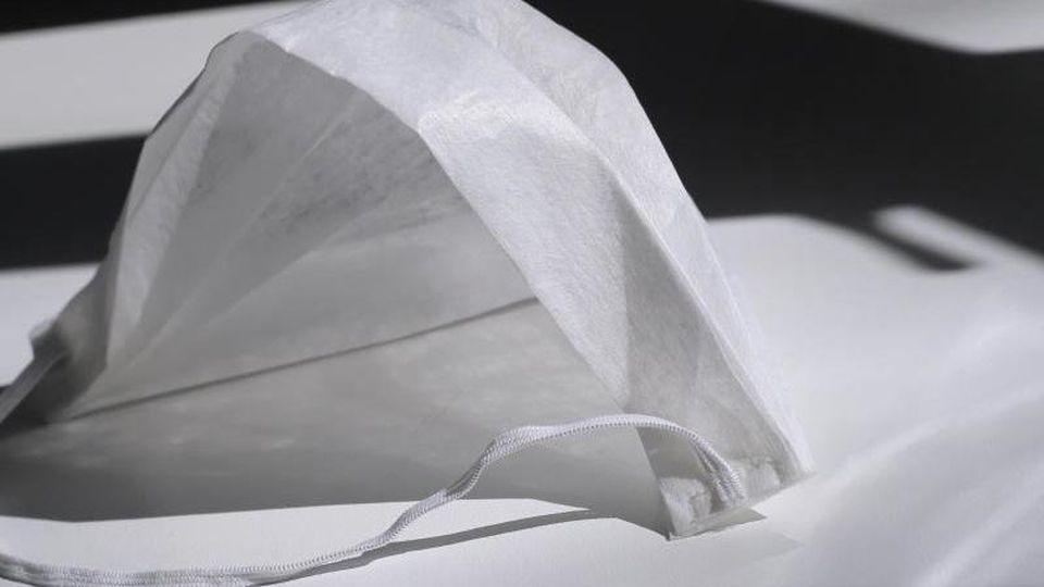 Ein medizinischer Mundschutz liegt auf einem Tisch im Sonnenschein. Foto: Karl-Josef Hildenbrand/dpa