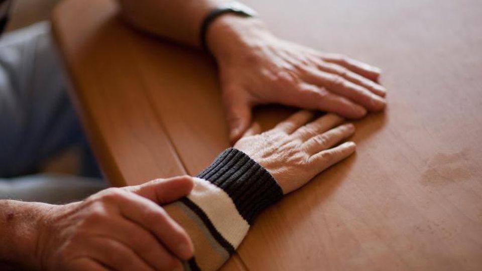 Ein Mann hält die Hand einer Frau, die an Alzheimer erkrankt ist. Foto: Oliver Killig/dpa-Zentralbild/dpa/Symbolbild
