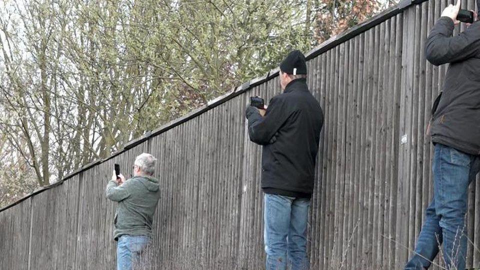 Schaulustige fotografieren neben einer Lärmschutzwand mit ihren Smartphones eine Unfallstelle. Foto: Alexander Auer/Archivbild