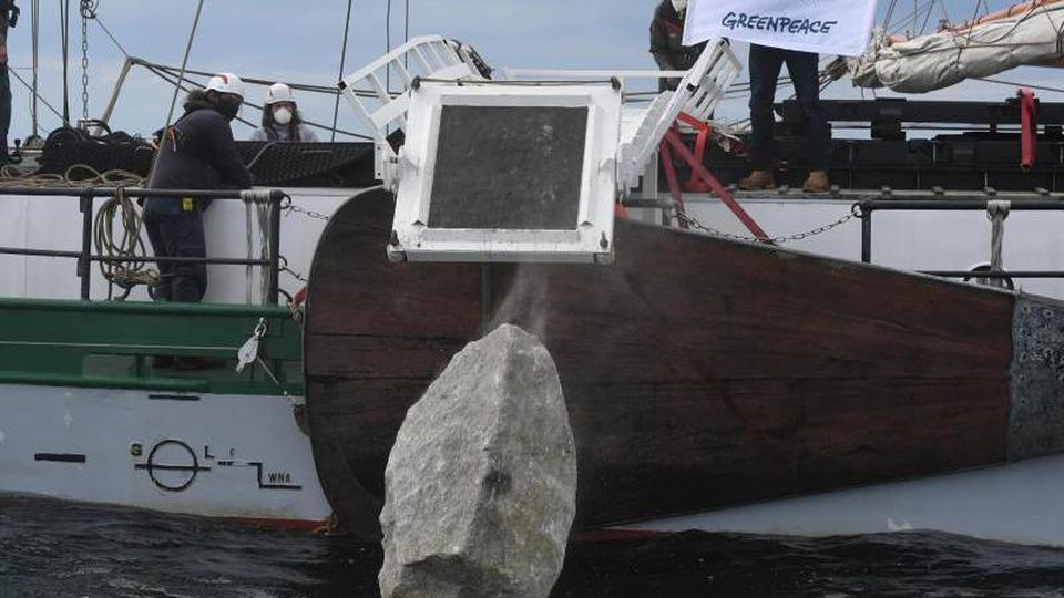 "Greenpeace-Aktivisten versenken vom Greenpeace-Schiff ""Beluga II"" aus große Granitblöcke im Meer. Foto: Stefan Sauer/dpa/Archivbild"