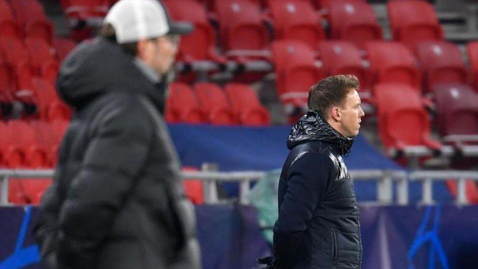 Liverpools Trainer Jürgen Klopp und Leipzigs Trainer Julian Nagelsmann (r) stehen am Spielfeldrand. Foto: Marton Monus/dpa