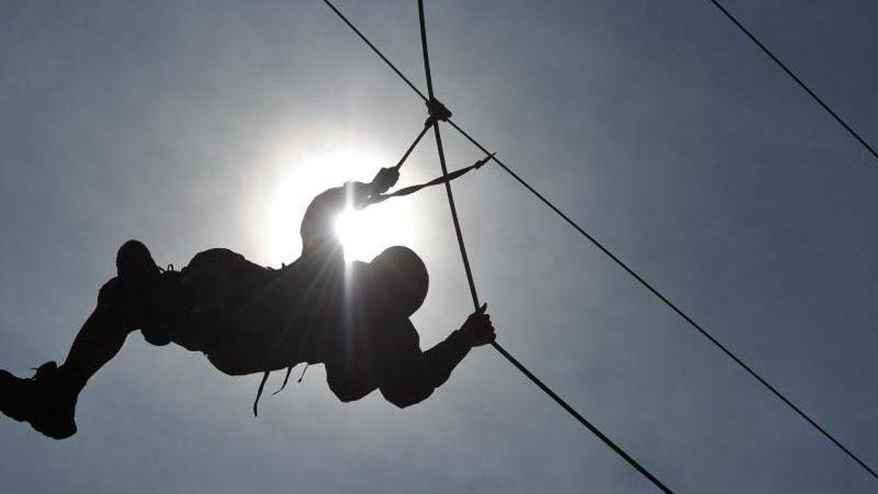 Ein Mann hangelt sich in einem Klettergarten an einem Seil entlang. Foto: picture alliance / dpa/Archivbild