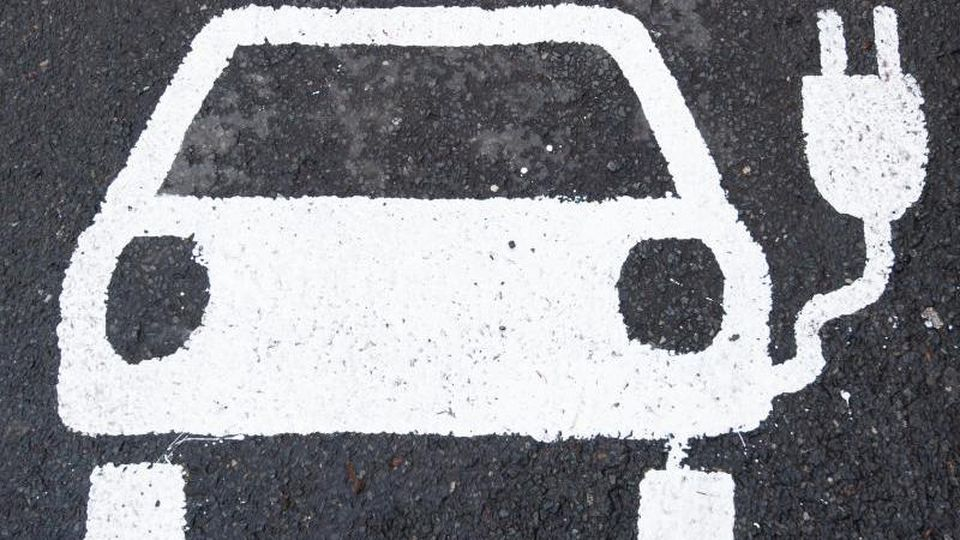 Ein Symbol für ein Elektroauto markiert einen Parkplatz neben einer E-Ladesäule. Foto: Julian Stratenschulte/dpa/Symbolbild
