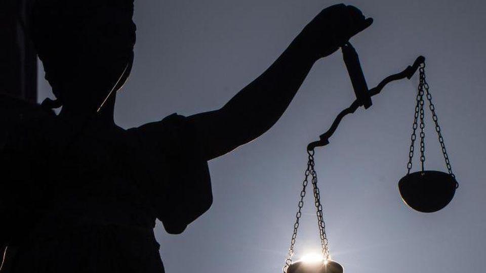 Die Statue der Justitia hält eine Waage in ihrer Hand. Foto: Frank Rumpenhorst/Archiv