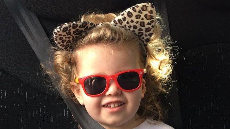 Ophelia Morgan-Dew, ein dreijähriges Mädchen mit einem IQ von 171, mit Leopardenohren und Sonnenbrille
