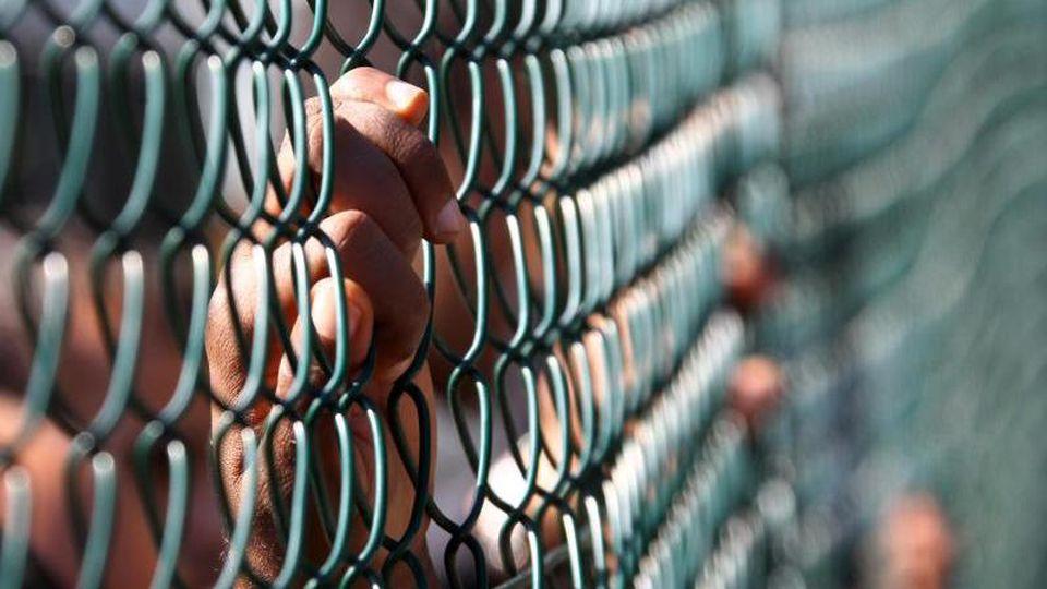 Die Hand eines Asylbewerbers hält sich am Außenzaun der Zentralen Aufnahmeeinrichtung für Flüchtlinge fest. Foto: Jens Büttner/Archiv