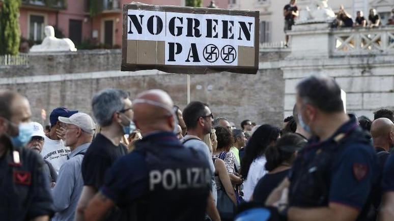 """Demonstranten und Mitglieder der rechtsextremen Organisation Forza Nuova halten ein Schild mit der Aufschrift """"No Green Pass"""" bei einem Protest gegen die Restriktionen des sogenannten Grünen Passes. Foto: Cecilia Fabiano/LaPresse via ZUMA Press/dpa"""