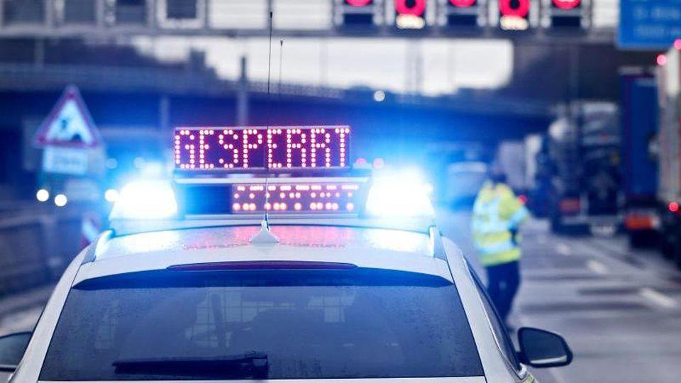 """Auf einem Polizeifahrzeug leuchtet die Aufschrift """"Gesperrt"""". Foto: David Young/dpa/Archivbild"""