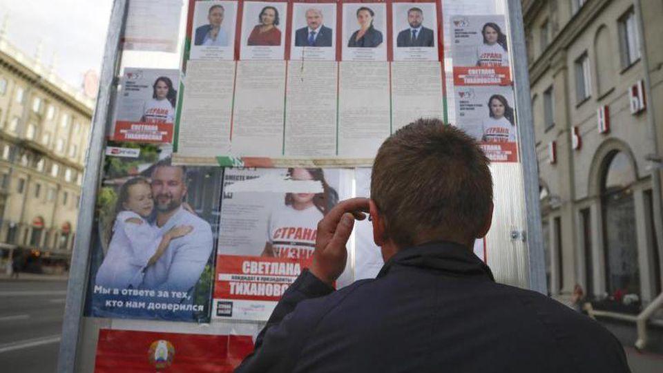 Ein Mann betrachtet Wahlplakate im Vorfeld der Präsidentenwahl. Foto: Sergei Grits/AP/dpa