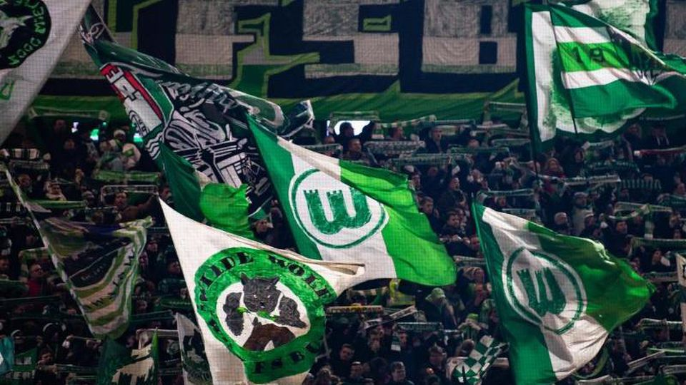 Fans des VfL Wolfsburg schwenken Fahnen. Foto: Swen Pförtner/dpa/Archivbild