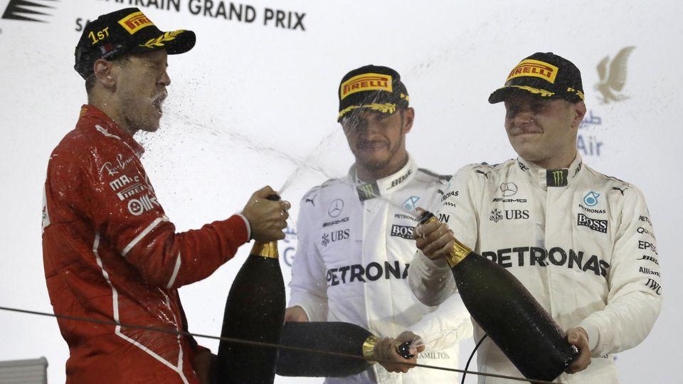 Motorsport: Formel-1-Weltmeisterschaft, Rennen, Grand Prix von Bahrain am 16.04.2017 in as-Sachir (Bahrain). Der Deutsche Sebastian Vettel vom Team Scuderia Ferrari (l) jubelt nach seinem Grand-Prix-Sieg. Neben ihm stehen der zweitplatzierte Brite Le