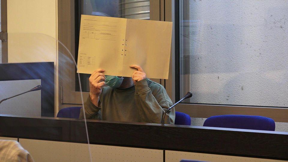 Der Vater versteckt sein Gesicht hinter seiner Akte.