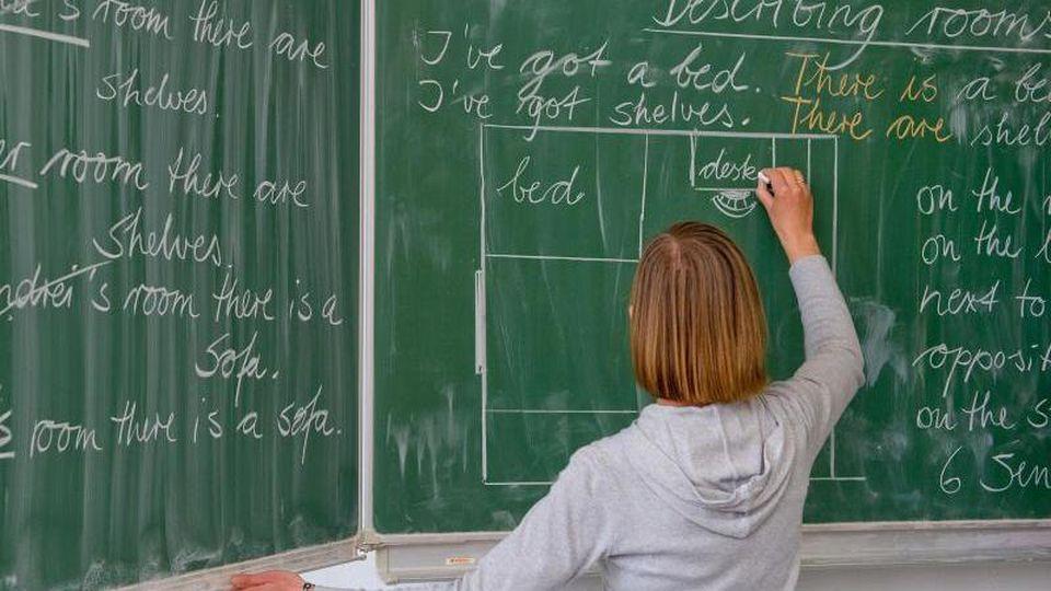 Eine Lehrerin einer Grundschule schreibt Unterrichtsinhalte an die Tafel. Foto: Patrick Pleul/dpa-Zentralbild/dpa