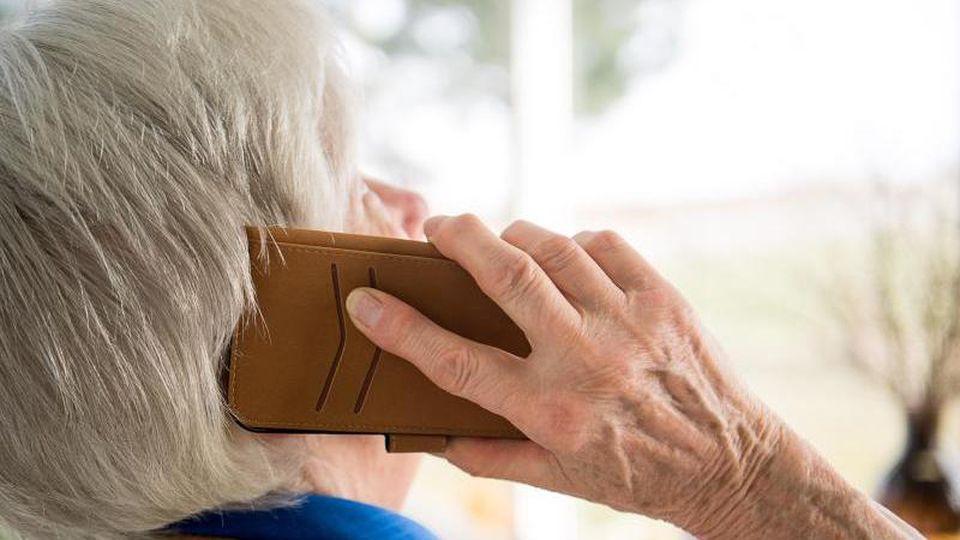 Eine Seniorin telefoniert mit ihrem Smartphone. Foto:SebastianGollnow/Archivbild