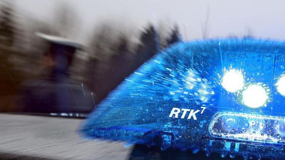 Ein Polizist steht neben einem Strefenwagen. Foto: Karl-Josef Hildenbrand/dpa/Symbolbild