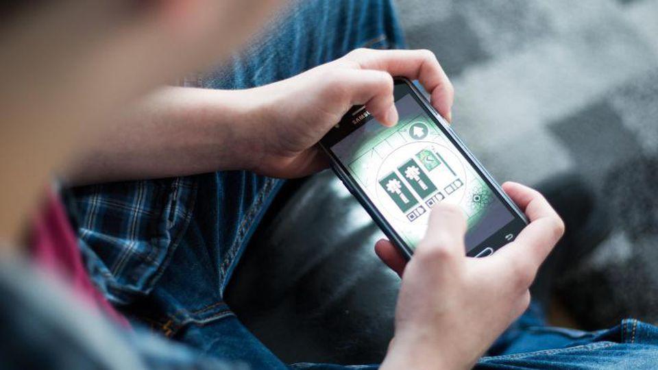 Ein Jugendlicher spielt in einem Wohnheim für computersüchtige Jugendliche mit einem Mobiltelefon. Foto: Marcel Kusch/dpa