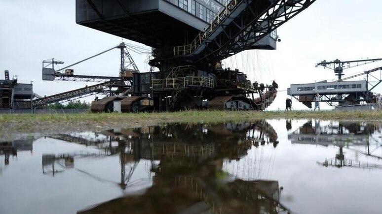 Ein ausgestelltes Bergbaugerät spiegelt sich in Ferropolis in einer Pfütze. Foto: Sebastian Willnow/dpa-Zentralbild/dpa/Archiv