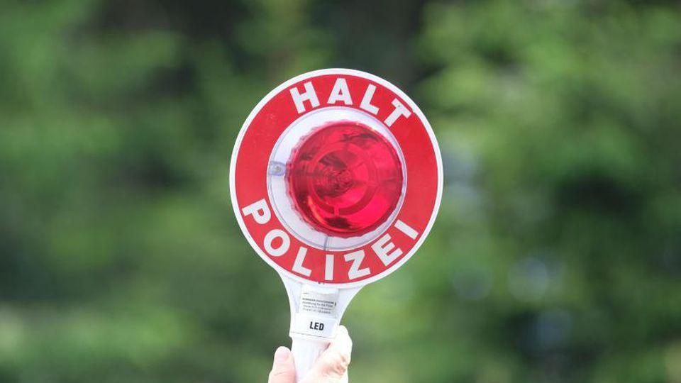 Eine Polizistin hält während einer Polizeikontrolle eine rote Winkerkelle in die Höhe. Foto: Sebastian Willnow/zb/dpa/Archivbild